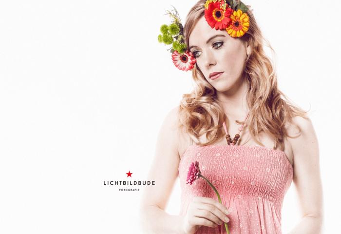 Nadine Petry in einem rosa Kleid und Blumen im Haar