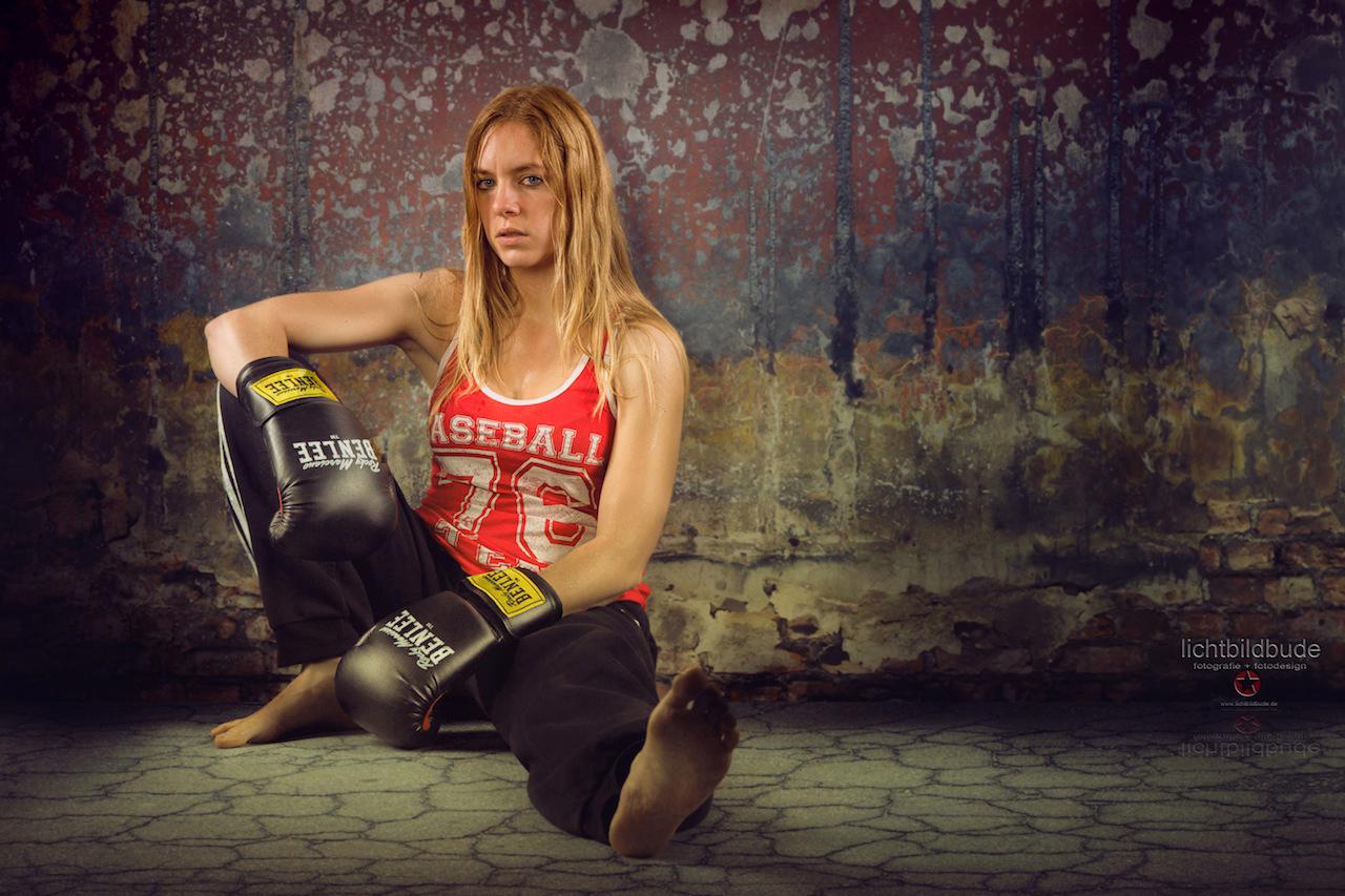 Nadien Petry nach dem Sport mit Boxhandschuhen am Boden sitzend