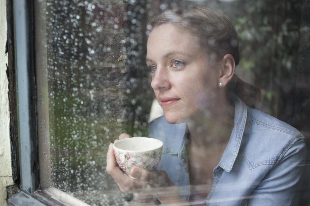 Nadine Petry hinter einer verregneten Fensterscheibe mit einer Tasse Tee