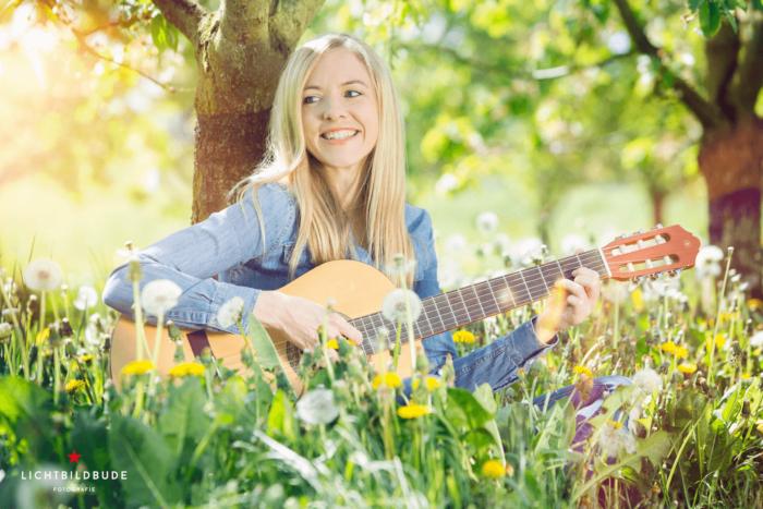 Nadine Petry sitzt mit einer Gitarre unter einem Baum in einer Blumenwiese