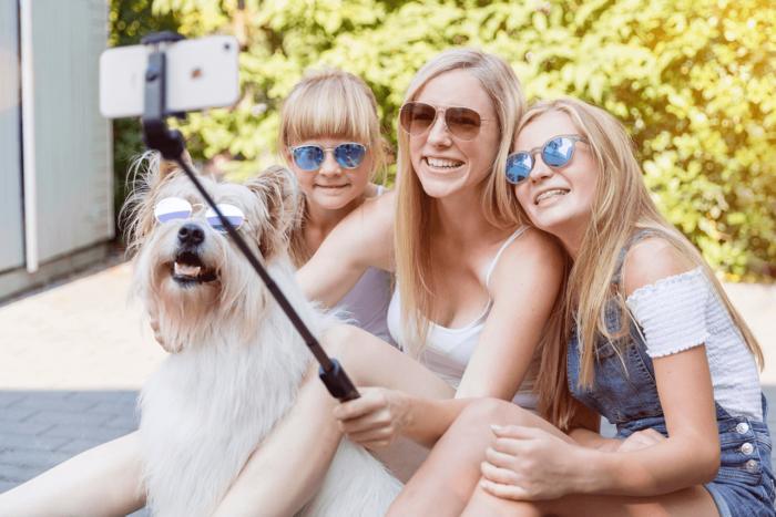 Nadine Petry macht mit zwei Kindern und einem Hund ein Selfie mit einem Selfiestick