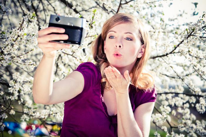Nadine Petry macht ein Selfie mit einem blühenden Kirschbaum im Hintergrund
