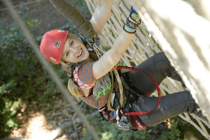 Nadine Petry klettert gesichert mit Gurt und Helm eine Wand hinauf