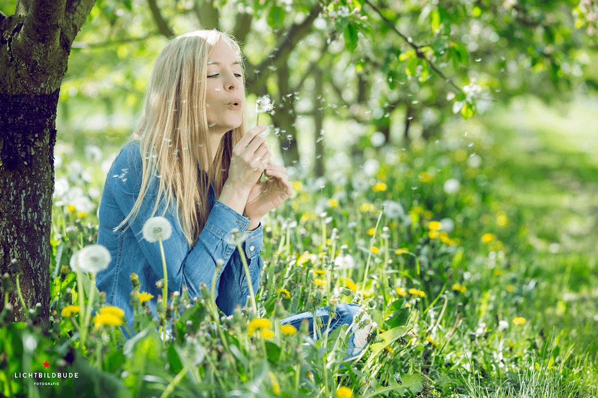 Nadine Petry sitzt in einer Wiese voller Löwenzahn und Pusteblumen unter einem Baum und pustet die Samen einer Blume in den Wind