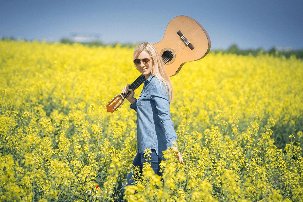 Nadine Petry mit Gitarre in einem blühenden Rapsfeld