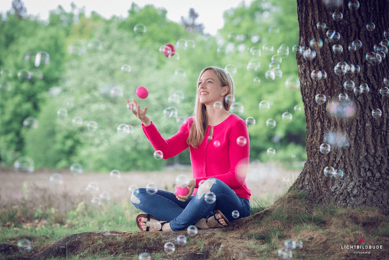 Nadine Petry sitzt jonglierend unter einem Baum. Im Vordergrund sind Seifenblasen.