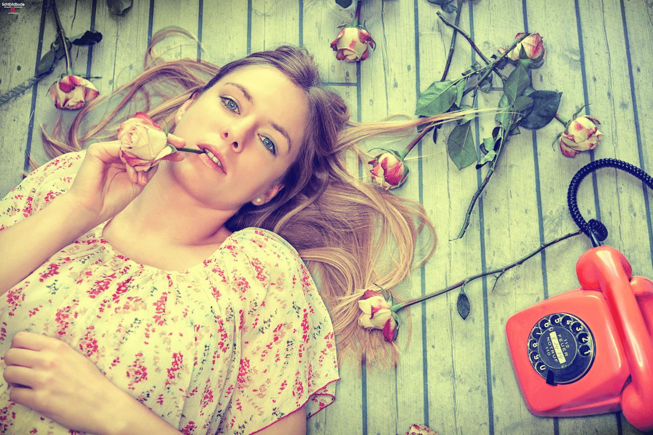 Nadine Petry liegt am Boden. Neben ihr ein rotes Telefon mit Wählscheibe