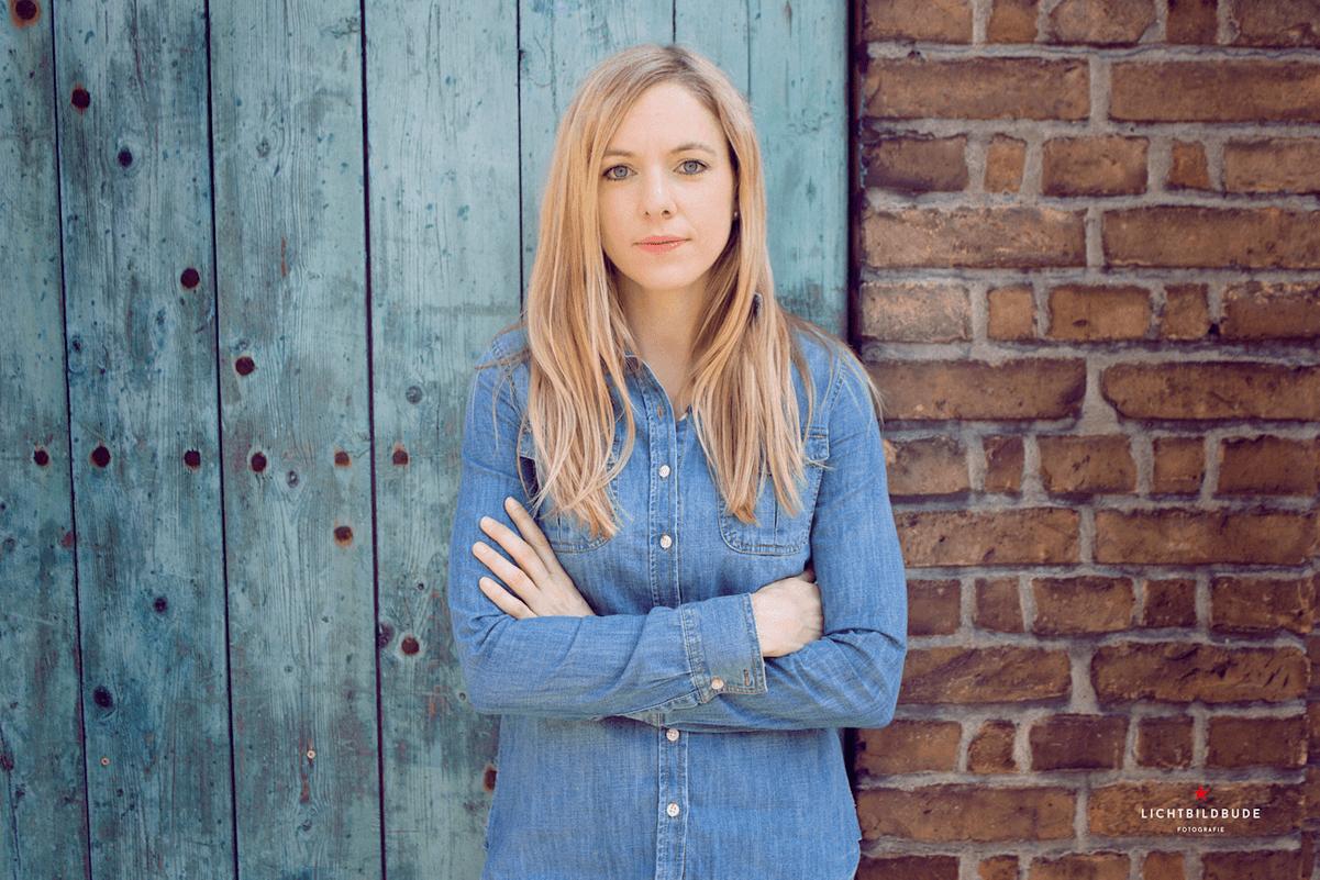Nadine Petry steht mit verschränkten Armen vor einer Ziegelwan mit einer alten blassblauen Holztür