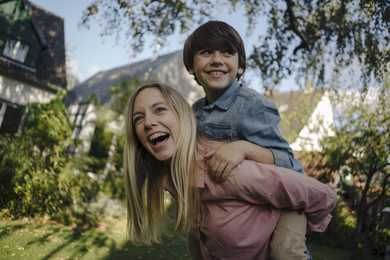 Nadine Petry mit einem Kind Huckepack auf dem Rücken.