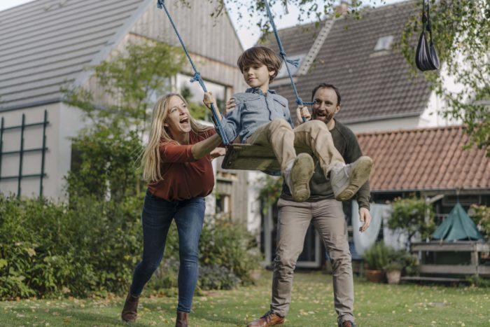 Nadine Petry mit einem männlichen Model und einem Kind auf der Schaukel.