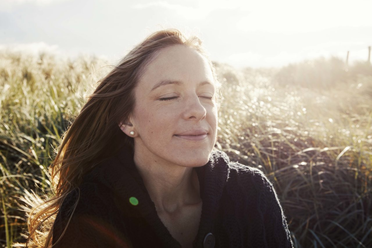 Nadine Petry mit geschlossenen Augen vor einer Düne.