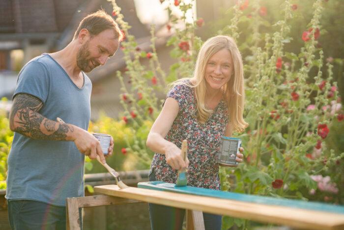 Nadine Petry und Joel Rakete streichen Bretter einer Gartenbank.