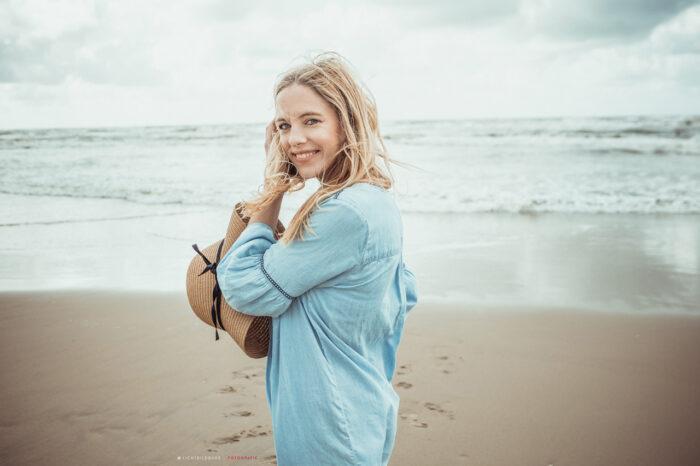 Nadine Petry mit Sonnenhut in der Hand am Strand.