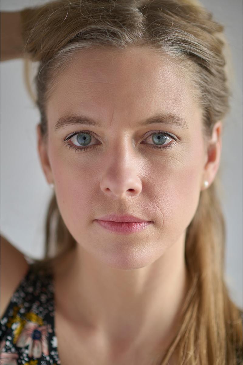 Nadine Petry im Porträt mit einer Hand am Hinterkopf