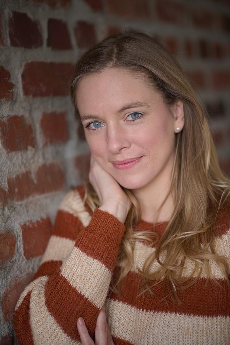 Nadine Petry vor einer roten Backsteinwand