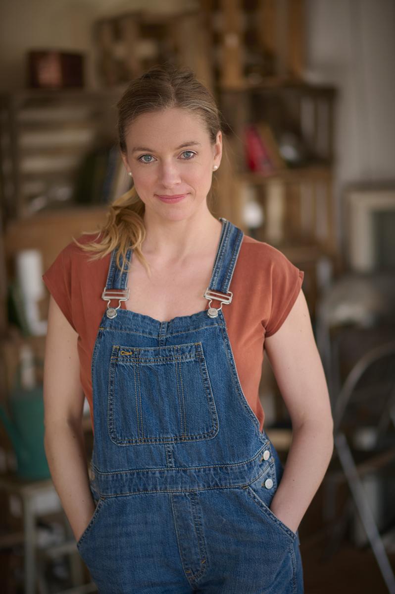 Nadine Petry in einer Latzhose mit einer Werkstatt im Hintergrund