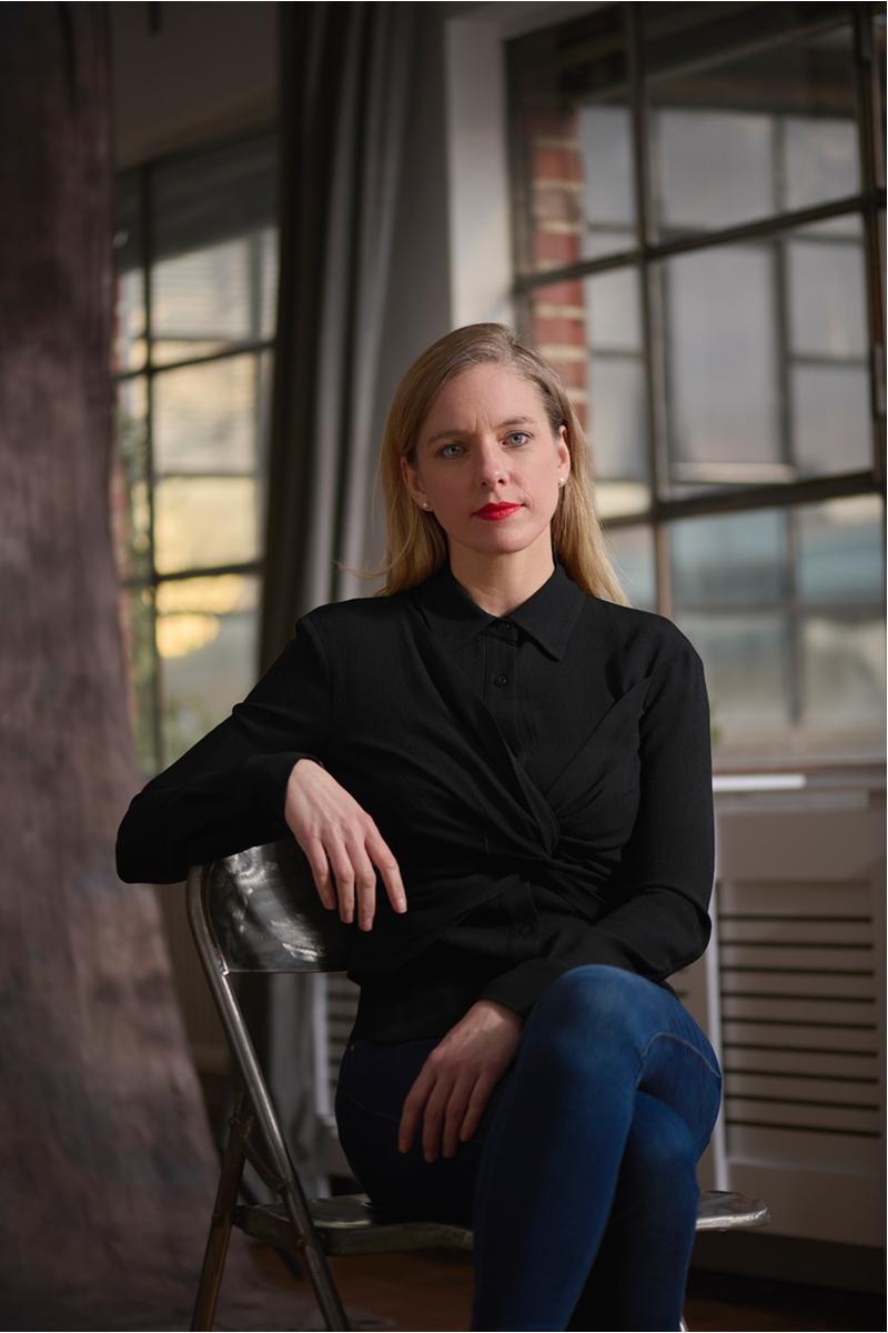 Nadine Petry sitzt auf einem Stuhl mit überschalgenen Beinen vor einem alten Industriefenster